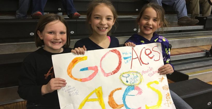3 girls as basketball game holding poster